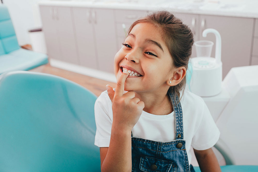 little girl smiling and pointing to her teeth