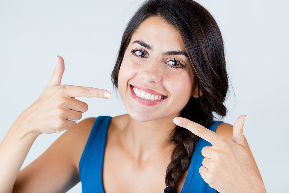 Young woman smiling and pointing to her teeth